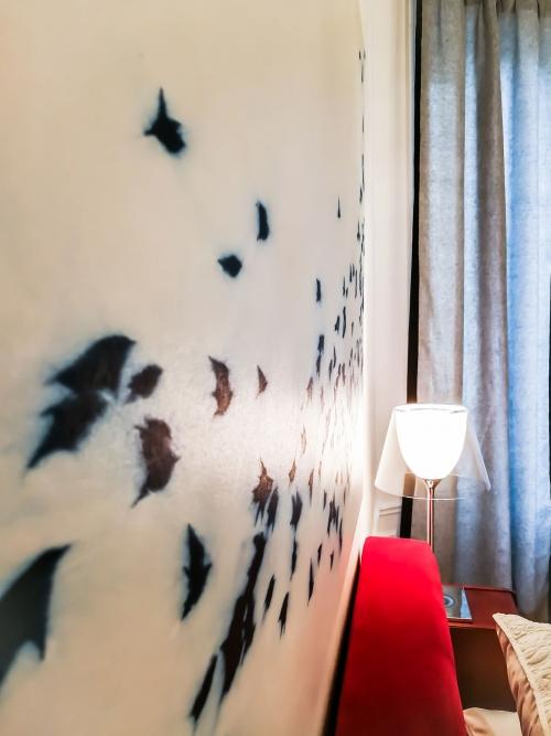 Beautifully designed master bedroom, with a featured artwork, beautful red velvet bed and flos table lamp. Interior design in Paris, by Authentic Interior design studio, Aida Sniraite